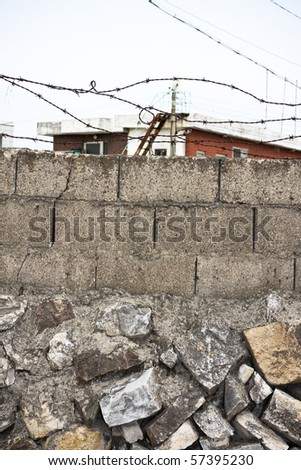 barbwire and stone wall - stock photo