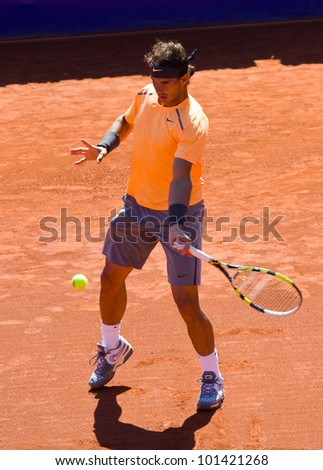 BARCELONA - APRIL 29: Spanish tennis player Rafael Nadal in action during his final match against David Ferrer at Barcelona tennis tournament Conde de Godo on April 29, 2012, in Barcelona, Spain. - stock photo