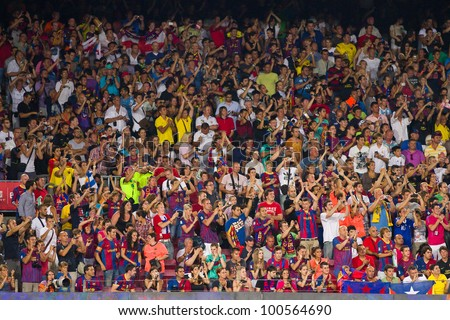 BARCELONA - AUGUST 17: FC Barcelona supporters celebrating a goal during the Spanish Super Cup final between FC Barcelona and Real Madrid, 3 - 2, on August 17, 2011 in Camp Nou, Barcelona, Spain. - stock photo