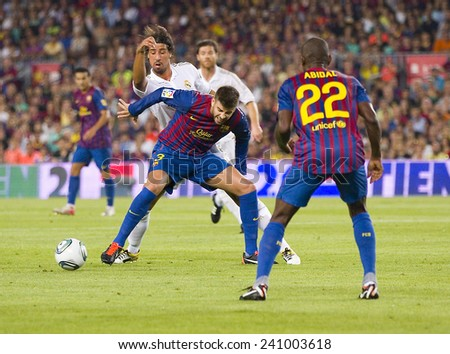 BARCELONA - AUGUST 17: Gerard Pique (midlle) in action at the Spanish Super Cup final match between FC Barcelona and Real Madrid, 3 - 2, on August 17, 2011 in Camp Nou stadium, Barcelona, Spain. - stock photo