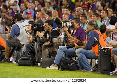 BARCELONA - AUGUST 17: Sport photographers working at the Spanish Super Cup final match between FC Barcelona and Real Madrid, 3 - 2, on August 17, 2011 in Camp Nou stadium, Barcelona, Spain. - stock photo