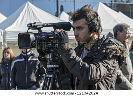 BARCELONA - DECEMBER 09: Cameraman TV covering the news of exhibition during the Montjuic Revival 2012. Barcelona Spain, December 09, 2012 - stock photo