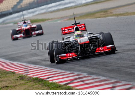 BARCELONA - FEBRUARY 19: Sergio Perez of Vodafone McLaren Mercedes F1 team leads Fernando Alonso in Ferrari at Formula One Test Days at Catalunya circuit on February 19, 2013 in Barcelona, Spain. - stock photo