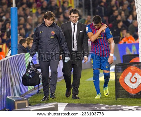 BARCELONA - JANUARY 25: Alexis Sanchez (R) and doctors at the Spanish Cup match between FC Barcelona and Real Madrid, final score 2 - 2, on January 25, 2012, in Camp Nou, Barcelona, Spain. - stock photo