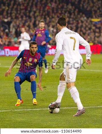 BARCELONA - JANUARY 25: Dani Alves (L) and Cristiano Ronaldo in action during the Spanish Cup match between FC Barcelona and Real Madrid, final score 2 - 2, on January 25, 2012, in Barcelona, Spain. - stock photo