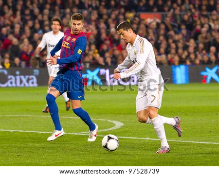 BARCELONA - JANUARY 25: Gerard Pique (L) and Cristiano Ronaldo in action during the Spanish Cup match between FC Barcelona and Real Madrid, final score 2 - 2, on January 25, 2012, in Barcelona, Spain. - stock photo