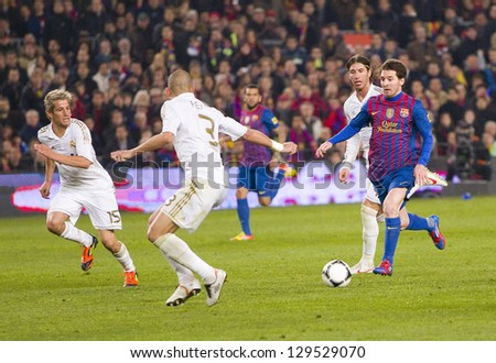 BARCELONA - JANUARY 25: Lionel Messi (R) of FCB in action at the Spanish Cup match between FC Barcelona and Real Madrid, final score 2 - 2, on January 25, 2012, in Barcelona, Spain. - stock photo