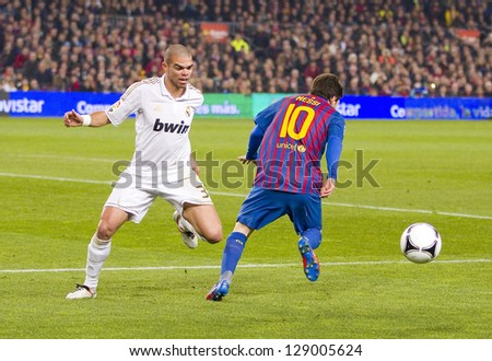 BARCELONA - JANUARY 25: Pepe Laveran (L) and Lionel Messi in action at the Spanish Cup match between FC Barcelona and Real Madrid, final score 2 - 2, on January 25, 2012, in Barcelona, Spain. - stock photo