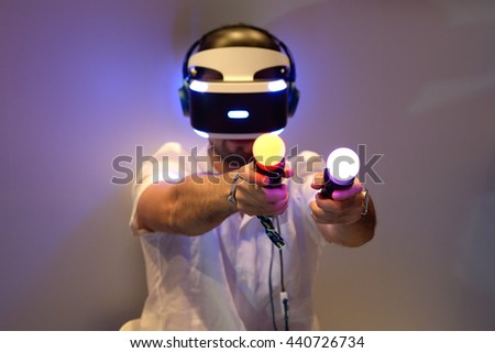 BARCELONA - JUN 16: A man tries the Playstation VR (Virtual Reality) glasses and the PlayStation Move motion controllers at Sonar Festival on June 16, 2016 in Barcelona, Spain. - stock photo