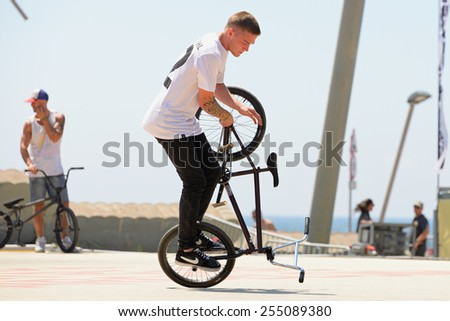 BARCELONA - JUNE 28: A professional rider at the BMX (Bicycle motocross) Flatland competition at LKXA Extreme Sports Barcelona Games on June 28, 2014 in Barcelona, Spain. - stock photo