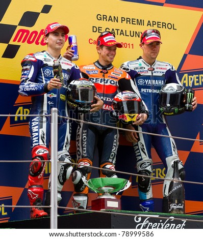 BARCELONA - JUNE 5: Casey Stoner (1st), Jorge Lorenzo (2nd) and Ben Spies (3dr) celebrating their trophies in the podium after the race of MotoGP of Catalunya, on June 5, 2011 in Barcelona, Spain. - stock photo