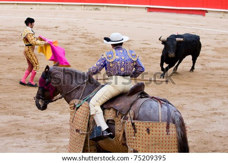 "BARCELONA - JUNE 6: Picador and torero in action during a ""corrida de toros"", typical Spanish tradition where a ""torero"" kills a bull. June 6, 2010 in Barcelona (Spain). - stock photo"