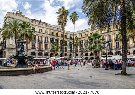 BARCELONA - JUNE 29, 2014: Tourists on Plaza Real in Barcelona, Spain. The Royal Plaza is a square in the Gothic Quarter. Located next to La Rambla and is a well-known tourist attraction. - stock photo