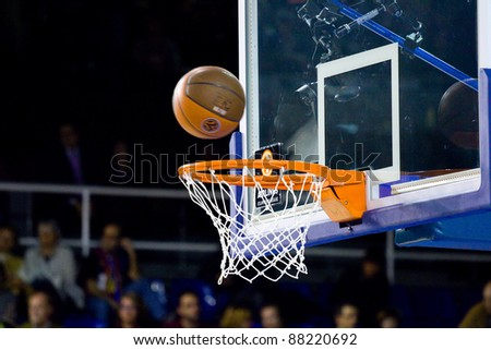 BARCELONA - MARCH 24: Ball inside the basket during the Euroleague basketball match between Barcelona and Panathinaikos, 71-75, on March 24, 2011 in Barcelona, Spain. - stock photo