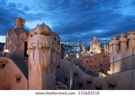 BARCELONA-MARCH 12: La Pedrera or Casa Mila, built and designed by Antoni Gaudi, with traffic lights, on March 12, 2013, Barcelona, Spain - stock photo