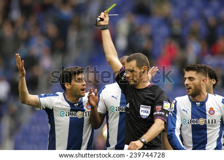 BARCELONA - MARCH, 29: Referee Clos Gomez delivers yellow card to RCD Espanyol players during a Spanish League match against FC Barcelona at the Estadi Cornella on March 29, 2014 in Barcelona, Spain - stock photo