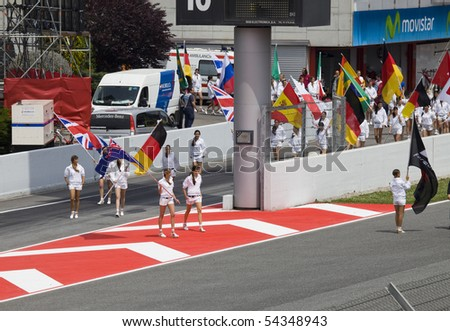 "BARCELONA - MAY 9: Girls leave with flags in honor of participants, autodrome ""Catalunya Montmello"" before beginning The Formula 1 Grand Prix on may 9, 2010 in Barcelona, Spain - stock photo"