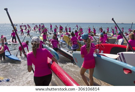 BARCELONA - MAY 23, 2015: Girls with surfboards paddle out to sea from the beach in Barcelona, Spain on May 23, 2015. - stock photo