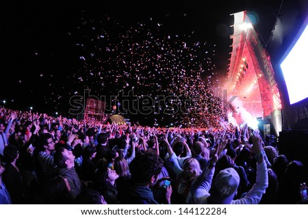 BARCELONA - MAY 23: People watching a concert, while throwing confetti from the stage at Heineken Primavera Sound 2013 Festival, Pitchfork Stage, on May 23, 2013 in Barcelona, Spain. - stock photo