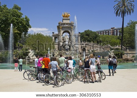 BARCELONA - MAY 23, 2015: Tourist group on bicycles at the fountain in the Ciutadella Park in Barcelona, Spain on May 23, 2015.