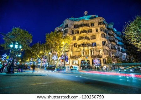 BARCELONA-NOVEMBER 24: La Pedrera or Casa Mila at dusk, built and designed by Antoni Gaudi, with traffic lights, on November 24, 2012, Barcelona, Spain - stock photo