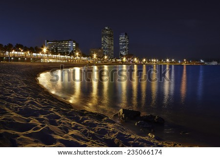 BARCELONA - OCTOBER 16: Barceloneta beach at dusk with Mapfre tower and Arts Hotel on October 16, 2014 in Barcelona, Spain