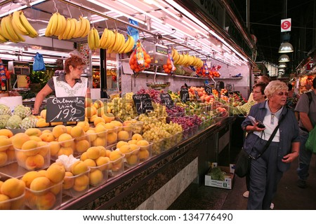 BARCELONA - OCTOBER, 2: Tourists in famous La Boqueria market on October 2, 2009 in Barcelona. One of the oldest markets in Europe that still exist. Established 1217. - stock photo