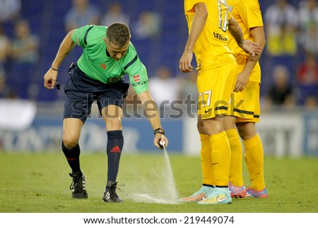 BARCELONA - SEPT, 20: Referee Iglesias Villanueva marks kick off positions with a Vanishing spray during a Spanish League match at the Estadi Cornella on September 20, 2014 in Barcelona, Spain - stock photo