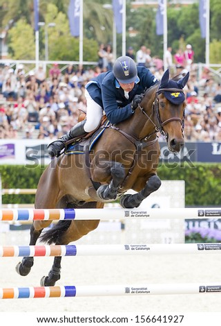BARCELONA - SEPTEMBER 28: Jens Fredricson from Sweden jumps a horse jumping obstacle at CSIO - Furusiyya Nations Cup Horse Jumping Consolation Competition, on September 28, 2013, in Barcelona, Spain.