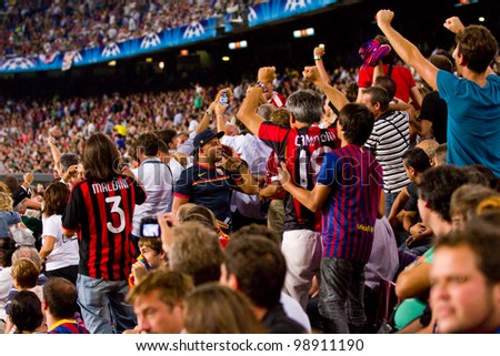 BARCELONA - SEPTEMBER 13: Unidentified Milan supporters celebrates a goal at the Champions League match between FC Barcelona and Milan, final score 2 - 2, on September 13, 2011, in Barcelona, Spain. - stock photo