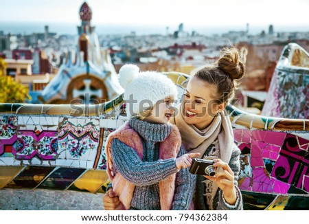 Barcelona signature style. Portrait of happy trendy mother and child travellers in Barcelona, Spain viewing photos on camera while sitting on a bench