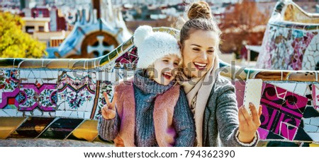 Barcelona signature style. Portrait of smiling trendy mother and daughter tourists in Barcelona, Spain with smartphone taking selfie while sitting on a bench
