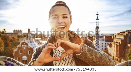 Barcelona signature style. smiling modern woman in coat at Guell Park in Barcelona, Spain showing heart shaped hands