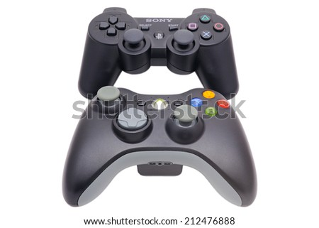BARCELONA, SPAIN - APR 18, 2014: The DualShock 3 wireless controller, a gamepad for the PlayStation 3 in front of its big rival of Microsoft Xbox 360 Controller, isolated on white background. - stock photo