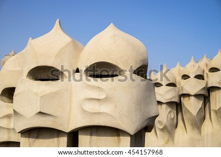 BARCELONA, SPAIN - APRIL 20. 2015: A series of chimneys on the roof of Casa Mila in Barcelona resemble soldiers in helmets. The building was designed by Antoni Gaudi. - stock photo