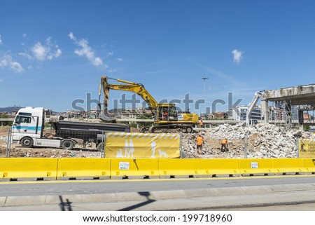 Barcelona, Spain - 28 April, 2014: excavator placing sand or debris on a truck. Pictured are several workers - stock photo