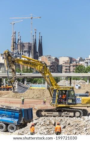 Barcelona, Spain - 28 April, 2014: excavator placing sand or debris on a truck with the Sagrada Familia in the background. Pictured are several workers - stock photo