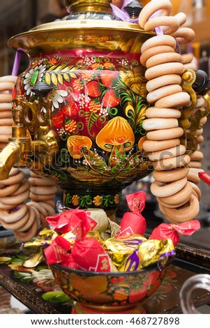 Barcelona, Spain - April 5, 2016: Khokhloma painting traditional Russian samovar with bunch of crackers bagels in Russian restaurant