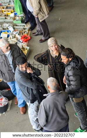 BARCELONA, SPAIN - APRIL 11, 2014: Some young people Arab race chat near the stall in the famous market Encants Vells in the city of Barcelona.