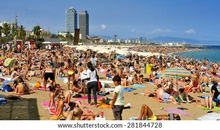 BARCELONA, SPAIN - AUGUST 19: A crowd of bathers in La Barceloneta Beach on August 19, 2014 in Barcelona, Spain. This popular beach hosts about 500000 visitors from everywhere during the summer season - stock photo