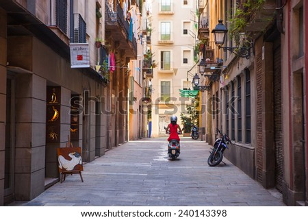 BARCELONA, SPAIN - AUGUST 12: Girl in red dress rides on a motor scooter on the street on  August 12, 2011 in Barcelona, Spain