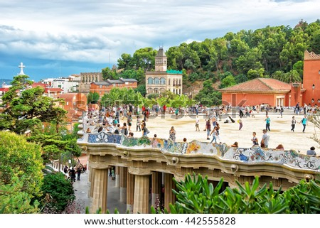 Barcelona, Spain - August 13, 2010: Tourists at Serpentine Bench in Park Guell in Barcelona in Spain. The bench is placed in main terrace in the shape of sea serpent. It was designed by Antoni Gaudi - stock photo