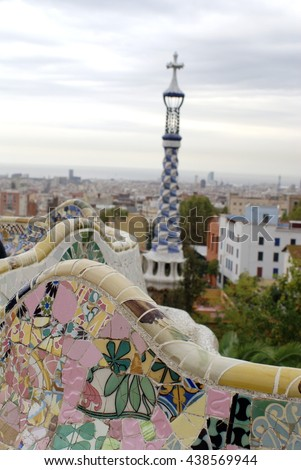 BARCELONA, SPAIN - CIRCA OCTOBER 2013: Tile mosaic terrace wall in Park Guell, with a tiled column beyond, and the city of Barcelona spread out in the distance
