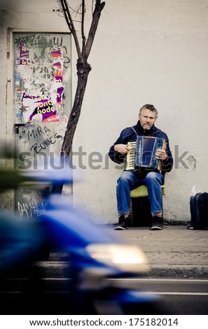 BARCELONA, SPAIN - 27 DECEMBER, 2013: A man sitting on a city street, playing with accordion, to get some money from the generosity of passersby. - stock photo