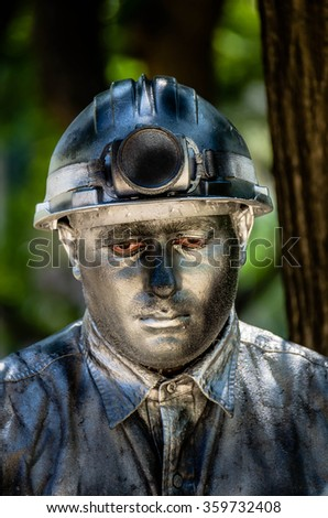 Barcelona, Spain - July 19, 2013: a miner with is protection helmet on is looking down with red eyes covered in silver color on his face in Barcelona Spain 2013 - stock photo