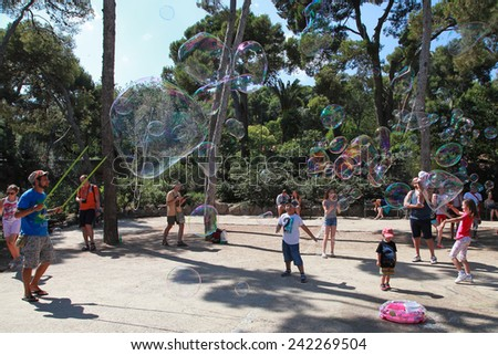 BARCELONA, SPAIN - JULY 8, 2014:  A street entertainer performs his bubble show for a group of tourists in famous Park Guell on July 8, 2014 in Barcelona, Spain.