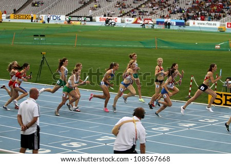 BARCELONA, SPAIN - JULY 15: athletes compete in the 4x400 relay race on the 2012 IAAF World Junior Athletics Championships on July 15, 2012 in Barcelona, Spain. - stock photo