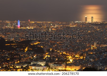 BARCELONA, SPAIN - JULY 12: Barcelona skyline at night with Agbar tower and Sagrada Familia standing out in the left on July 12, 2014 in Barcelona. - stock photo