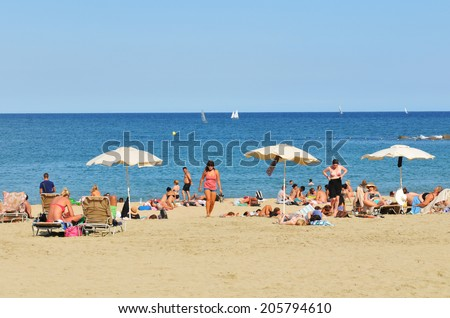 BARCELONA, SPAIN - JULY 6, 2012: Crowds of tourists enjoy the sun on the beach in Barcelona - stock photo