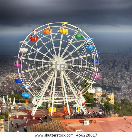 BARCELONA, SPAIN - JULY 20, 2016:Ferris wheel in Tibidabo with panoramic view over Barcelona. It is located at free access area of Tibidabo Amusement Park. Before storm